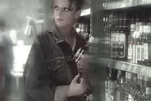 Woman hiding a liquor bottle in her jean jacket within a retail store, with no loss prevention in place to deter her