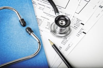 stethoscope sitting on top of a stack of medical bills