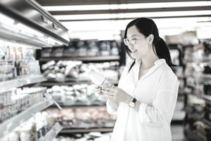 Woman looking at a new beverage in her supermarket.
