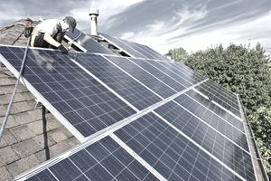 Man installing solar panels on the roof of a Green Home.