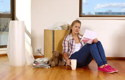 Tenant in an apartment leaning against a packing box and reading a notice