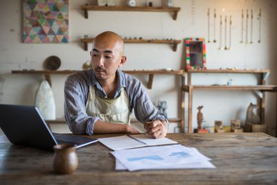 Storekeeper in a rural shop at a rustic desk doing bookkeeping