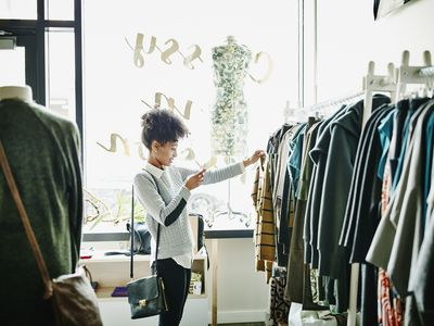 Woman taking photo of clothing with smartphone