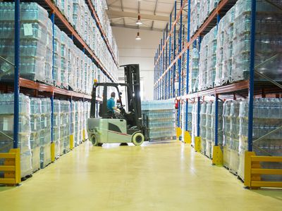 A worker moving pallets with forklift in warehouse.