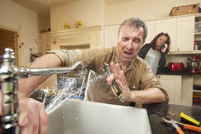 Man trying to fix his sink while water sprays in his face.