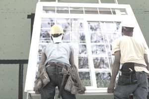 Carpenters positioning a large window frame at a construction site