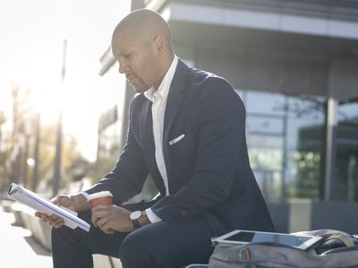 Businessman reading a recycling trade magazine while sitting outside with a cup of coffee