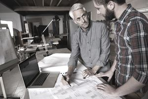 Father and son looking at documents for their family business.