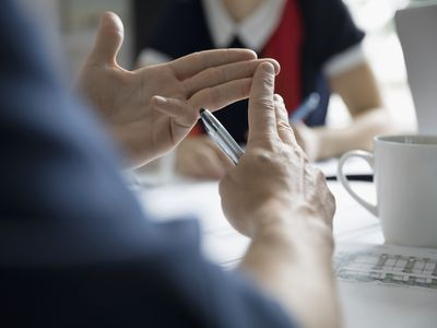 Close up of hands of person making points in meeting