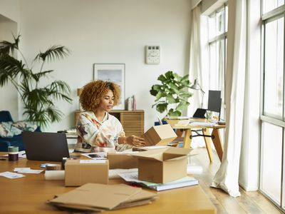 Woman working on laptop and packing boxes