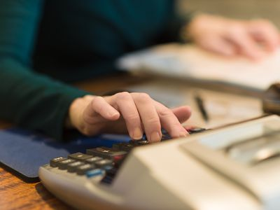 Woman using a calculator at her desk to work as a CPA, bookkeeper, or accountant.