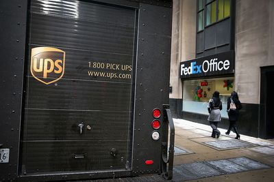 A UPS delivery truck sits in front of a FedEx