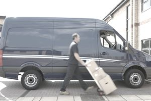 Blurred view of Caucasian delivery man wheeling packages