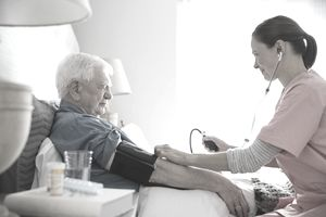 Home care nurse taking senior mans blood pressure
