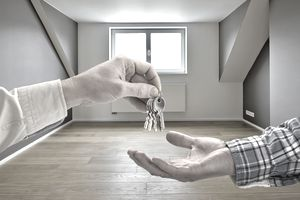 one person handing keys to another