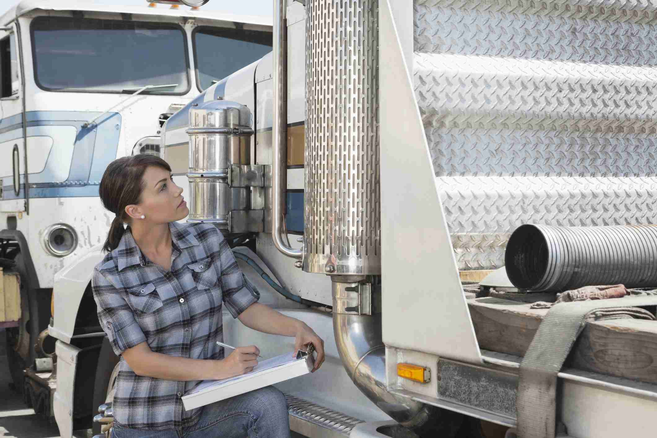 woman inspecting a commercial vehicle without the driver present