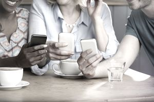 Three friends using smartphones at a coffee shop
