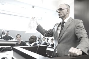 "A grey-haired gentleman lawyer stands at the podium in a court room and holds up a document marked ""Evidence"" in his right hand."