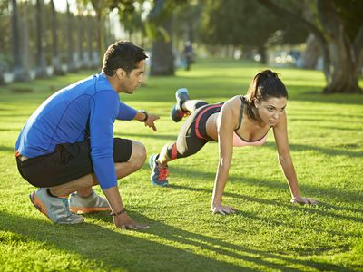 a personal trainer working with a young woman