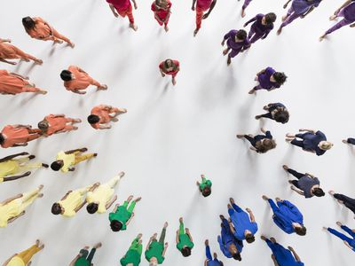 Overhead view of a group of people separated by the color of their clothing into segments of a circle.