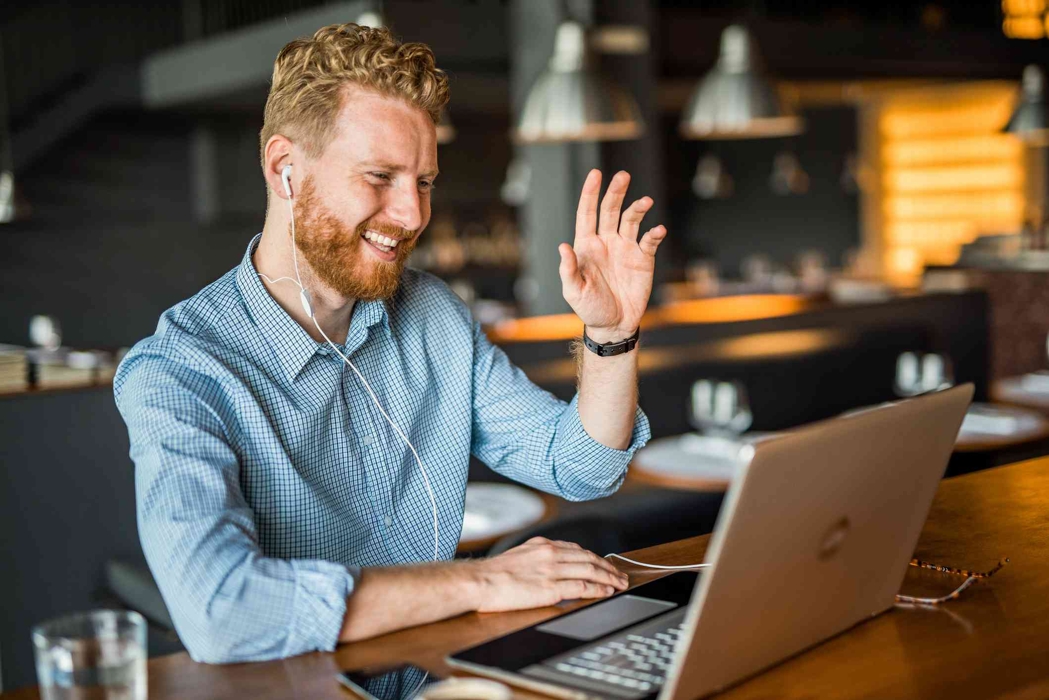 Happy young businessman waving to an online client