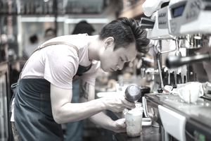 Barista making an espresso drink in a coffee shop.