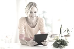 Woman looking at a non-profit website using tablet at home