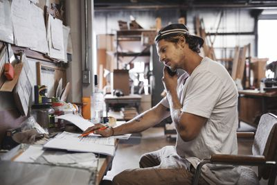 Small business owner on phone doing paperwork in workshop