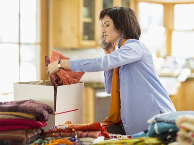 A woman packing scarves into a box