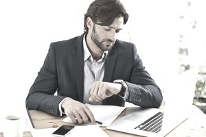 Man at laptop looking at watch