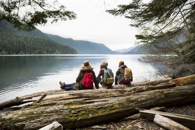 Three hikers sitting by a lake.