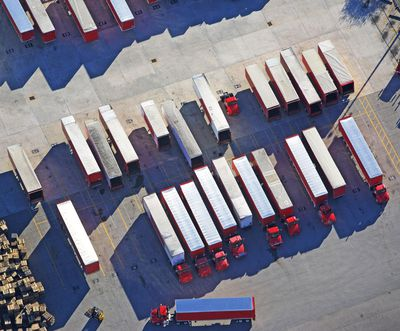 Overhead view of several commercial semi trucks at a loading dock