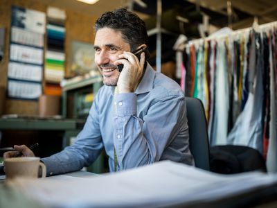 Happy mature businessman sitting at his desk talking on cordless phone. Fashion shop owner having telephonic conversation with client.
