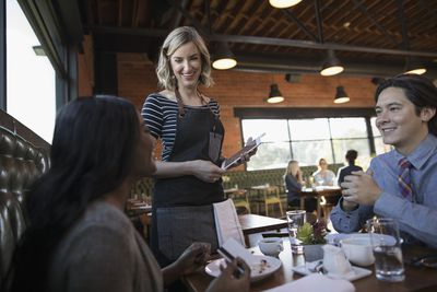 Couple dining, paying server with digital tablet credit card swiper at restaurant table