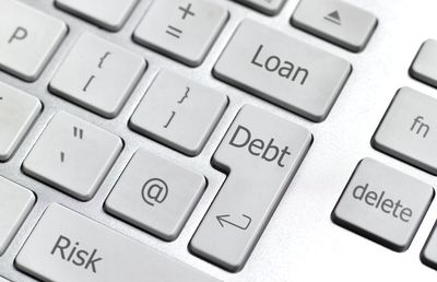 a computer keyboard with debt, loan, and risk keys