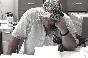 Small business owner on the phone in his back office, overwhelmed with paperwork for his tax returnss