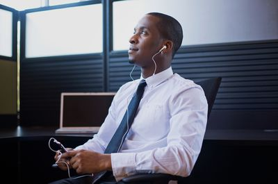 Man in dress shirt and tie sitting in office listening to phone through headphones