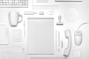 Assorted home office desk accessories including a spiral notebook, mug, mouse, calculator, and pen