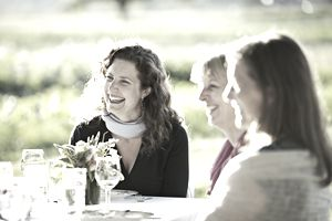 Female friends laughing with each other at dinner