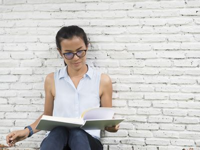 Woman reading against a wall