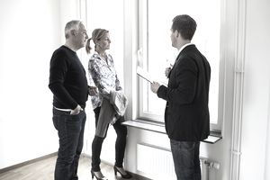 Male real estate agent discussing with couple at home