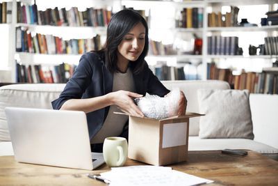 a woman packing a box for shipping