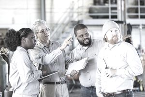 One woman, three men in a factory work setting, looking and pointing at something.