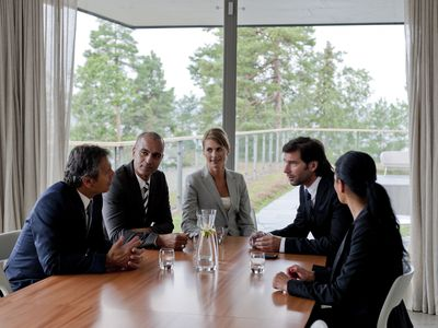 Three business men and 2 business woman are seated around a table at a meeting