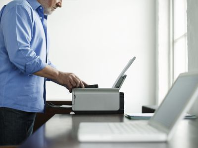 Man standing by wireless printer with computer in the foreground