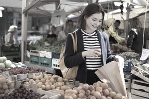 a woman shopping for fruit at outdoor market
