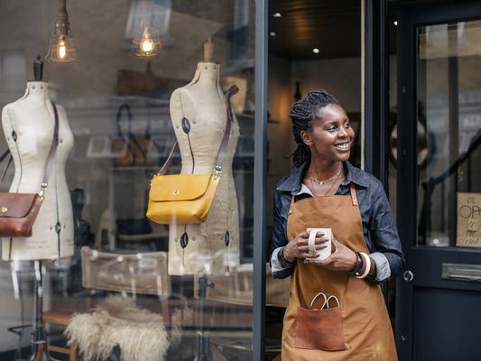 A small business owner stands outside her handbag shop.