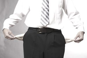 Businessman showing his empty pockets, representing debt.