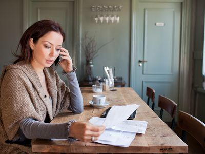 Woman on cell phone with paperwork in restaurant