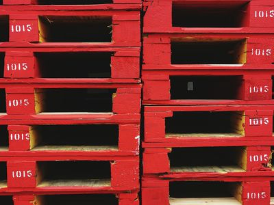 a close up of a stack of Red Pallets for rent